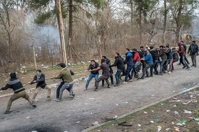 Na zdjęciu: Migranci na granicy Turcji z Grecją próbują obalić grecki płot graniczny i wkroczyć do Grecji w pobliżu Edirne w Turcji 4 marca 2020 roku. (Zdjęcie: Bulent Kilic/AFP via Getty Images)
