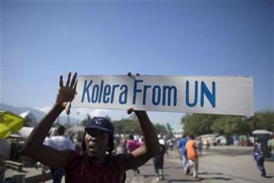 Protestujący trzyma plakat podczas demonstracji przeciwko misji ONZ w Port-au-Prince 18 listopada 2010. (Zdjęcie: REUTERS)