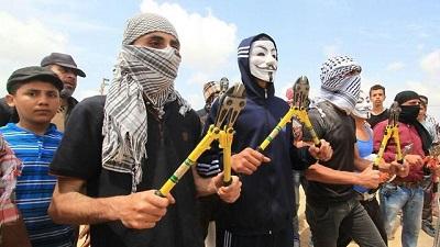 Pokojowi demonstranci z nożycami do przecinania granicznego płotu.