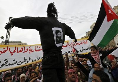 Jordańscy demonstranci niosą kukłę przywódcy ISIS, Abu Bakr al-Baghdadiego w Ammanie w lutym 2015 roku, po ukazaniu się wideo z makabrycznym mordem pilota, Muatha Al-Kaseasbeha. (zdjęcie: MUHAMMAD HAMED/REUTERS)