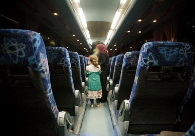 """Na zdjęciu: Członkowie rodzin syryjskich """"Białych Hełmów"""", uratowani przez Izrael, w autobusie, który przetransportował ich do Jordanii 22 lipca. (Zdjęcie: IDF)"""