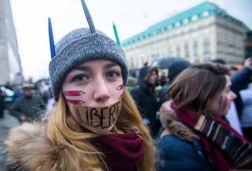 Kobieta z ustami zaklejonymi plastrem z napisem 'Liberte' na ustach podczas marszu solidarności w Paryżu. (zdjęcie: REUTERS)