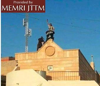 Wojownicy IS umieszczają swoją flagę na kościele w Sindżar