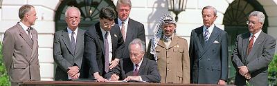 <span>Porozumienia z Oslo podpisano w Białym Domu dokładnie 25 lat temu, 13 września 1993 r. |Szimon Peres, minister spraw zagranicznych Izraela, podpisuje, a premier Izraela Icchak Rabin, prezydent Bill Clinton i Jasser Arafat oraz Mahmoud Abbas z OWP przyglądają się. [</span>Zdjęcie: J David AKE/AFP<span>]</span>