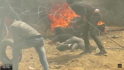 Na zdjęciu: Palestyńczycy w Gazie próbują przedrzeć sie przez płot graniczny z Izraelem korzystając z zasłony dymnej. 30 marca 2018. (Zrzut z ekranu z wideo Ateya Bahar).