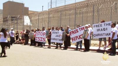 Kiedy kilku prześladowanych chrześcijan irackich przekroczyło granicę USA, zostali wtrąceni do więzienia na kilka miesięcy, a potem odesłani do krajów, które ich prześladowały, na możliwą niewolę, gwałty lub śmierć. Na zdjęciu powyżej: członkowie społeczności chrześcijan irackich w Kalifornii i ich sympatycy protestują przeciwko wielomiesięcznemu internowaniu starających się o azyl chrześcijan irackich w ośrodku internowania Otay Mesa. (Zrzut z ekranu z programu Al-Dżaziry)<br />