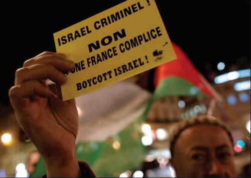 We Francji zwolennik Palestyny trzyma ulotkę popierającą bojkot Izraela. (zdjęcie: REUTERS)