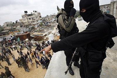 Islamski Dżihad od dnia swojego założenia nie przyniósł Palestyńczykom w rządzonej przez Hamas Strefie Gazy niczego poza nieszczęściem, zniszczeniem i śmiercią. Na zdjęcie: Terroryści z Islamskiego Dżihadu obserwują tłum z dachu meczetu 27 marca 2010 r. w Chan Jounis w Strefie Gazy. (Zdjęcie: Warrick Page/Getty Images)