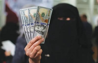 Urzędniczka Hamasu w Gazie pokazuje dolarowe banknoty po otrzymaniu pensji wypłaconej przez Katar w grudniu 2018 roku(zdęcie: IBRAHEEM ABU MUSTAFA/REUTERS)