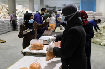 Dla zapobieżenia szerzeniu się koronawirusa (choroby COVID-19) w północnej części Strefy Gazy pracownicy pakują żywność do dystrybucji przez UNRWA i dostarczenia do domów palestyńskich uchodźców, 31marca 2020, (zdjęcie: REUTERS/MOHAMMED SALEM)