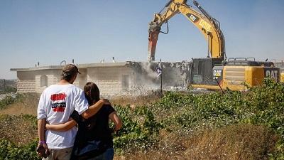 Małżeństwo Izraelczyków patrzy na dźwig, który burzy dom w nielegalnej żydowskiej dzielnicy Netiv Ha'avot w Gusz Ecjon, dwa dni po eksmisji mieszkańców, 14 czerwca 2018. Zdjęcie: Gershon Elinson/Flash90.