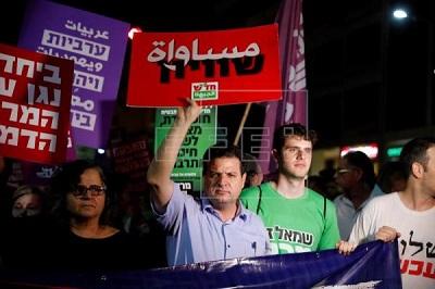 """Arabski poseł do Knesetu, Ayman Odeh, wznosi na placu Rabina w Tel Awiwie transparent z napisem """"Równość"""" podczas protestu przeciw konstytucyjnej ustawie o państwie żydowskim. 14 lipca 2018 EPA-EFE/ABIR Sultan"""