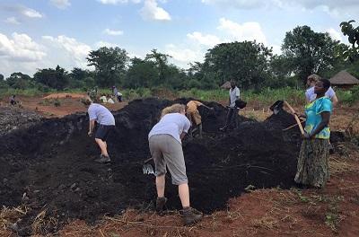 Farmerzy i wolontariusze pracują z organicznym nawozem w ośrodku Uganda Community Farm. (Zdjęcie: UCF)