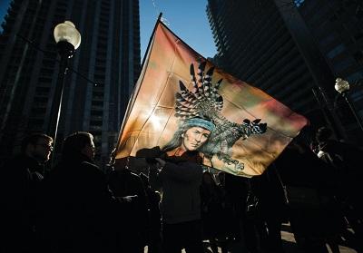 Sylwetki protestujących z Pierwszego Narodu widoczne za flagą podczas demonstracji w Toronto w 2013 r. (zdjęcie: REUTERS)