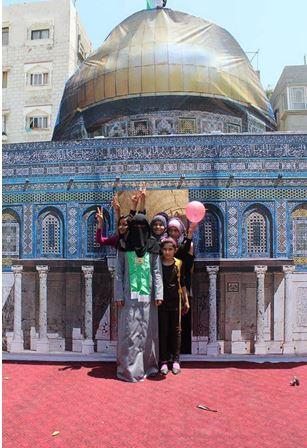 Dziewczynki z wychowawczynią z obozu obok modelu meczetu Al-Aksa (Facebook.com/Camp.west.Gaza2014, 15 czerwca 2014)