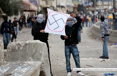 Palestyńscy demonstranci trzymają swastykę w antyizraelskim proteście na Zachodnim Brzegu.(Zdjęcie: REUTERS)