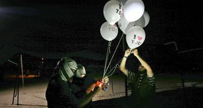 """Zamaskowani Palestyńczycy, nazywający siebie """"jednostkami nocnego zamieszania"""", trzymają zapalające urządzenia przyczepione do balonów, który wypuszczą w stronę Izraela. Zdjęcie z granicy między Gazą a Izraelem na wschód od Rafah z 26 września 2018. (Zdjęcie: KHATIB/AFP via Getty Images)"""