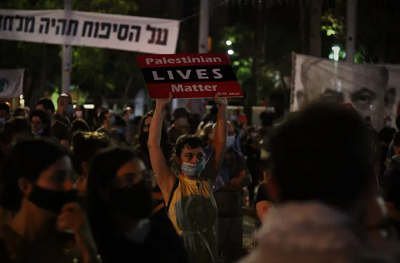 """<span>Protestujący w Tel Awiwie niosą transparent """"Palestyńskie Życie Się Liczy"""" (Zdjęcie: LEON SVERDLOV)</span>"""