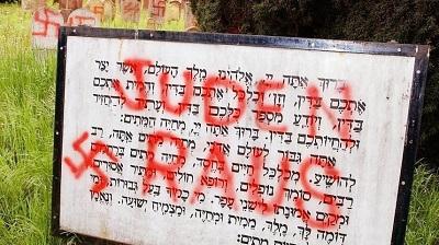 """Napis """"Juden Raus"""" wymalowany na tablicy przy wejściu na żydowski cmentarz w Herrlisheim, we wschodniej Francji (zdjęcie AP)."""