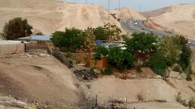 Finansowany przez społeczność międzynarodową budynek szkolny w Chan al-Achmar, z izraelską autostradą Nr 1 w tle. (Zdjęcie: TrickyH/Wikimedia Commons)