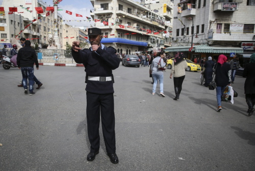 Palestyński policjant kieruje ruchem na głównym placu w mieście Ramallah na Zachodznim Brzegu, 23 lutego 2014. Zdjęcie: Hadas Parush / Flash90