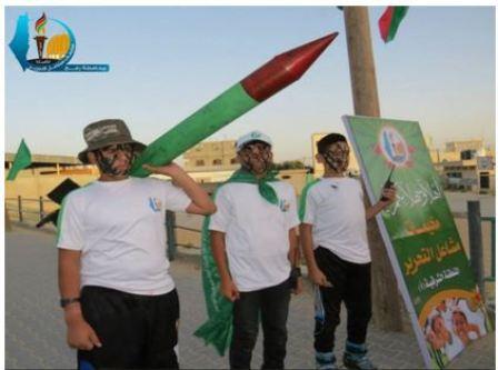 Dziecko niosące atrapę rakiety; plakat reklamuje obozy letnie (Facebook.com/Gazacamps2014, 17 czerwca 2014)