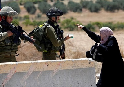 Palestyńska kobieta w sprzeczce z żołnierzami izraelskiej armii na punkcie kontrolnym w obozie uchodźców Al-Fawwar na Zachodnim Brzegu na południe od Hebronu (zdjęcie: REUTERS/MUSSA QAWASMA)
