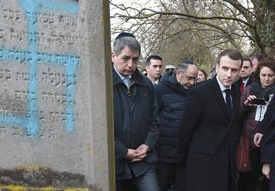 Emmanuel Macron patrzy na grób z wymalowaną swastyką podczas wizyty na żydowskim cmentarzu w Quatzenheim 19 lutego. (zdjęcie: FREDERICK FLORIN/POOL/VIA REUTERS)