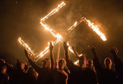 Członkowie Ruchu narodowosocjalistycznego oddają nazistowski salut pod płonącą swastyką. Georgia, USA. 21 kwietnia 2018. (zdjęcie: GO NAKAMURA/REUTERS)