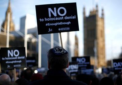 Protestujący trzymają plakaty i flagi podczas demonstracji zorganizowanej przez British Board of Jewish Deputies przeciwko antysemityzmowi na Parliament Square w Londynie. (zdjęcie: HENRY NICHOLLS/REUTERS)