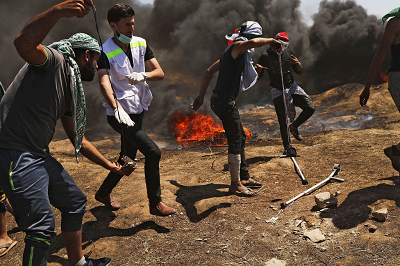 Na zdjęciu: Grupa Palestyńczyków podczas rozruchów przy granicy z Izraelem 14 maja 2018 r. Dwóch młodych mężczyzn przygotowuje atak procami na izraelskich żołnierzy. (Zdjęcie: Spencer Platt/Getty Images)