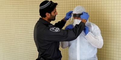 <span>Izraelski policjant pomaga inspektorowi z Ministerstwa Zdrowia w nałożeniu ochronnej odzieży przed wejściem do mieszkania osoby w kwarantannie jako środku ostrożności przed szerzeniem się koronawirusa. Hadera, Izrael, 16 marca 2020. Zdjęcie: Reuters / Ronen Zvulun.</span>