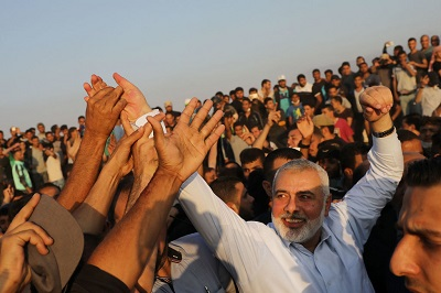 """Z jednej strony, Hamas wysyła Palestyńczyków, by prowokowali izraelskich żołnierzy na granicy Gazy z Izraelem pod hasłem """"Nie dla negocjacji [z Izraelem]"""". Z drugiej strony, Hamas błaga Egipcjan i ONZ, by pomogli zaaranżować zawieszenie ognia z Izraelem. Na zdjęciu: przywódca Hamasu, Ismail Hanija pozdrawia protestujących w Gazie przy płocie granicznym z Izraelem, 15 maja 2018 roku. (Zdjęcie: Spencer Platt/Getty Images)"""