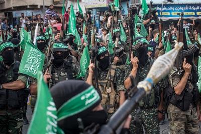 Hamas i Islamski Dżihad rządzą niemal dwoma milionami Palestyńczyków w Strefie Gazy. Każda grupa ma własne kierownictwo polityczne, jak również milicje, które posiadają różne rodzaje broni, w tym rakiety i pociski balistyczne. Na zdjęciu: Bojówkarze Hamasu paradują ze swoją bronią w Gazie 20 lipca 2017 r. (Zdjęcie: Chris McGrath/Getty Images)