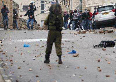 MŁODZIEŻ PALESTYŃSKA ciska kamieniami w żołnierzy armii izraelskiej podczas starć w mieście Ramallah na Zachodnim Brzegu w piątek. (zdjęcie: REUTERS)