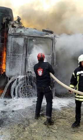 Agent IHHpróbuje wygasić ogień spowodowany bombardowaniem rosyjskim.Na jego plecach widać wyraźnie logo IHH. (Zdjęcie: Hurriyet, 26 listopada 2015)