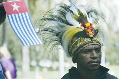 """Mężczyzna w tradycyjnym nakryciu głowy stoi obok flagi """"Gwiazdy porannej"""" podczas wiecu w Sydney w Australii, w poparciu Zachodnich Papuasów.(photo credit: WILL BURGESS/REUTERS)"""
