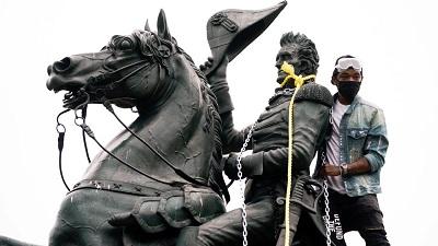 Podczas gdy Black Lives Matter (BLM) i jego sykofanci bez końca debatują o zmianach nazw ulic i usuwaniu pomników, ignorują osłupiające 40 milionów ofiar rzeczywistego niewolnictwa w dzisiejszym świecie, włącznie z około 9,2 milionami mężczyzn, kobiet i dzieci obecnie żyjących jako niewolnicy w Afryce. Na zdjęciu: Wandale próbują obalić pomnik prezydenta USA, Andrew Jackson na Lafayette Square, 22 czerwca 2020, w pobliżu Białego Domu w Waszyngtonie.