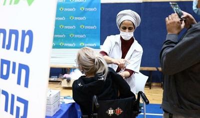 Gazety i media elektroniczne po obu stronach Atlantyku dokonują akrobatycznych wysiłków, by prowadzić nagonkę na Izrael z powodu nadzwyczajnego sukcesu w szczepieniach przeciwko koronawirusowi. Na zdjęciu: Pielęgniarka izraelska szczepi kobietę w środkowym Izraelu 28 grudnia 2020 (Gideon Sharon/ GPO)