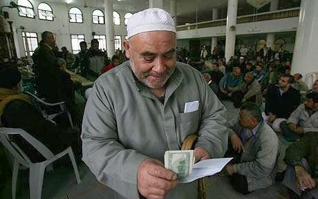 """Zdjęcie ilustrujące artykuł w """"Telegraph"""" informujący o tym, jak terroryści kontrolują i poskramiają populację Gazy przez rozdawania gotówki [Image Source]."""