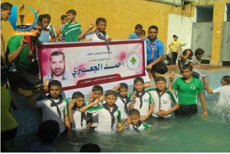 Dzieci w basenie przed portretem byłego szefa militarnego skrzydła Hamasu, Ahmeda Al-Dżabariego (Facebook.com/Gazacamps2014, 19 czerwca 2014)