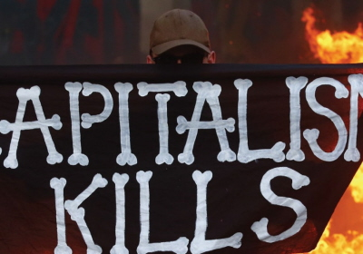Protestuj±cy przeciwko G20 stoi przed p³on±c± barykad± uliczn± podczas zamieszek w Hamburgu (zdjêcie: REUTERS)