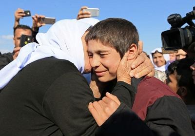 Krewny całuje ocalałego jazydzkiego chłopca po jego uwolnieniu z rąk bojówkarzy Państwa Islamskiego w Syrii, w Duhok w Iraku, 2 marca 2019. (zdjęcie: ARI JALAL / REUTERS)