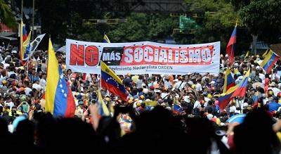 """Demonstranci z transparentem """"nie chcemy więcej socjalizmu"""" podczas wiecu opozycji z udziałem opozycyjnego przywódcy Juana Guaido, w Caracas 2 lutego 2019.<div></div>"""