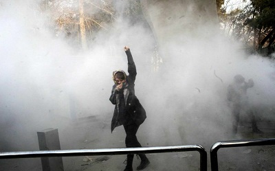 Na zdjęciu: młoda kobieta protestuje, podczas gdy w tle irańskie siły bezpieczeństwa rozpędzają tłum gazem łzawiącym.