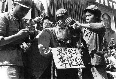 """Czerwonogwardziści umieszczają plakat na szyi mężczyzny, oskarżając go o to, że jest członkiem """"czarnej klasy"""" w 1966 roku."""