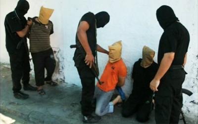 Zamaskowani członkowie Hamasu (ubrani na czarno) przygotowują egzekucję miejscowych Palestyńczyków, którzy, jak twierdzą, szpiegowali na rzecz Izraela, 22 sierpnia 2014, w Gazie. (Zdjęcie: Reuters, zrzut z ekranu)