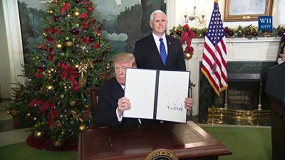 Prezydent Donald Trump pokazuje podpisaną \