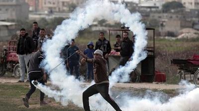 Palestyński uchodźca pokojowo protestuje przy płocie granicznym.