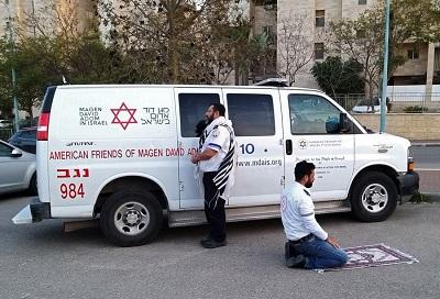 Dwóch paramedyków modli się koło ambulansu American Friends of Magen Adom (AFMDA) w #TelAviv, Żyd z Ber Szewy zwrócony ku Jerozolimie, a muzułmański Arab z Rahat zwrócony ku Mekce (Zdjęcie z Twittera: Shiraz Hassan#PhotooftheDay)